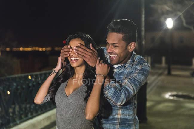 Coppia in città di notte, scherzare, uomo che copre gli occhi della donna con le mani, Lisbona, Portogallo — Foto stock