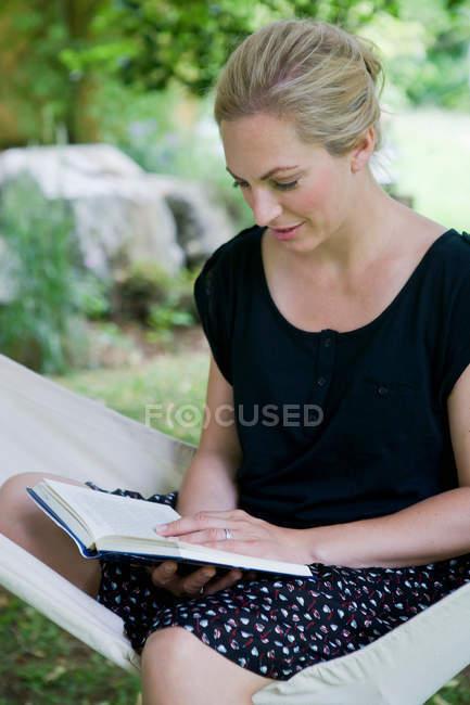 Woman reading book in hammock — Stock Photo