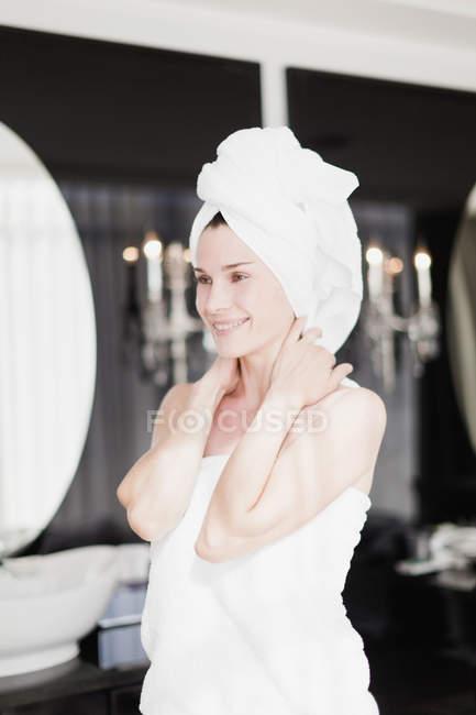 Donna avvolta in asciugamani in camera da letto — Foto stock