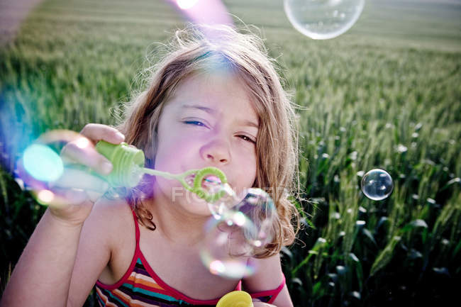 Girl blowing bubbles to camera — Stock Photo