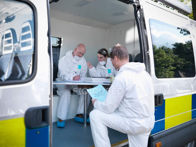 Forensic scientists sitting in police incident van at crime scene — Stock Photo