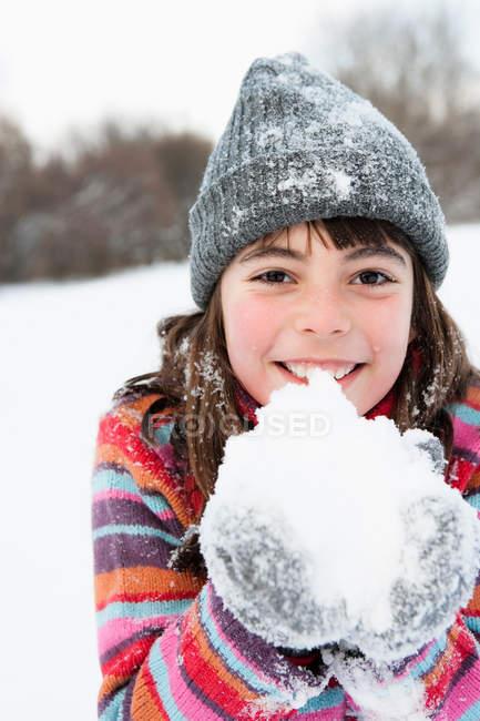 Девушка держит снег в руках — стоковое фото