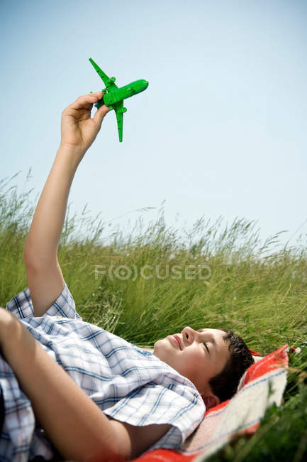 Boy lying down playing with plane — Stock Photo