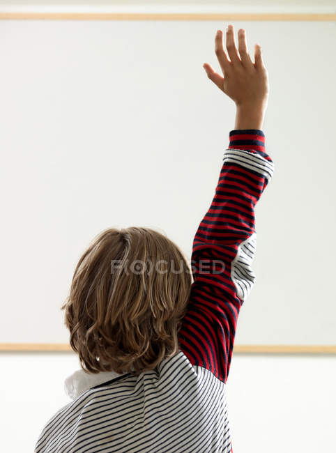 Rear view of boy raising hand in classroom — Stock Photo