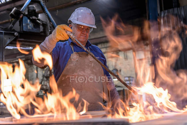 Worker using flames to cure a mould in foundry — Stock Photo