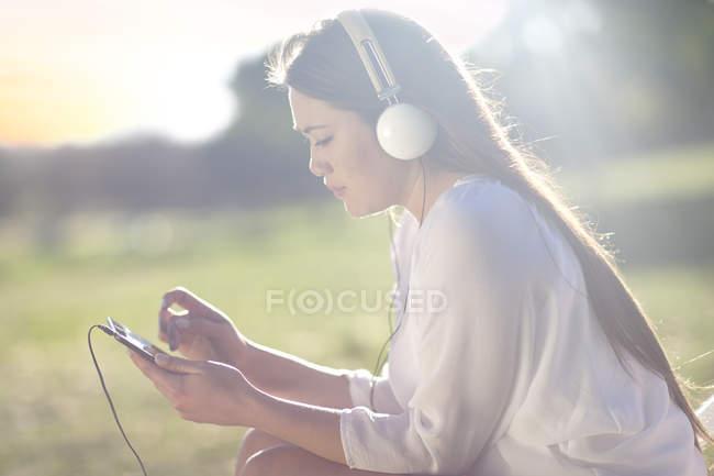 Retrato de mujer joven con tableta digital y auriculares - foto de stock