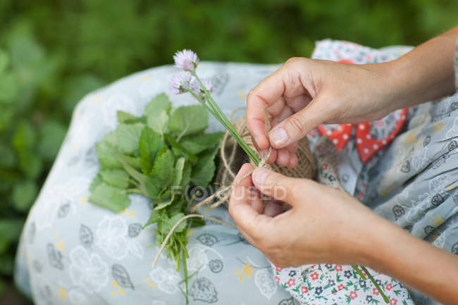 Cropped shot of woman tying string around flowers — Stock Photo