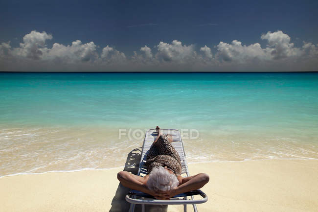 Senior Woman relaxing on beach — Stock Photo