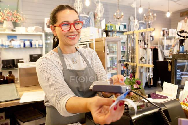 Помощница продавщицы принимает оплату кредитной картой при выезде в сувенирном магазине — стоковое фото