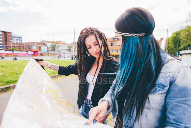 Two young women with dreadlocks and dyed hair pointing at map in urban park — Stock Photo