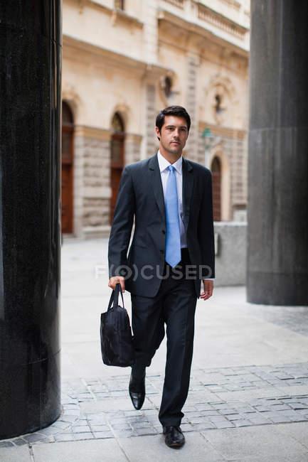 Businessman walking on city street — Stock Photo