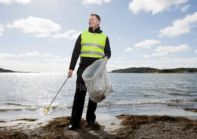 Worker in safety vest cleaning beach — Stock Photo