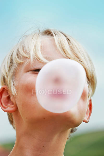 Smiling boy blowing bubble outdoors — Stock Photo