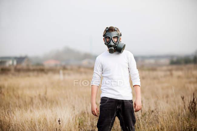 Boy wearing gas mask in wheat field — Stock Photo