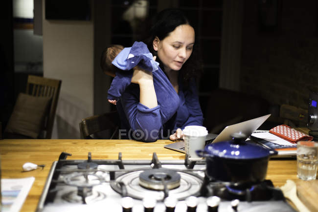 Mother cradling newborn son and using laptop on kitchen bar — Stock Photo