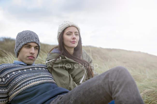 Coppia giovane seduta sulla spiaggia, Brean Sands, Somerset, Inghilterra — Foto stock