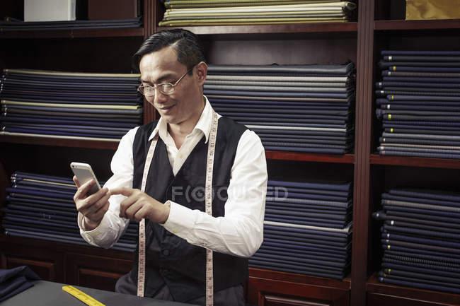Портной смс на мобильный телефон в магазине портных — стоковое фото