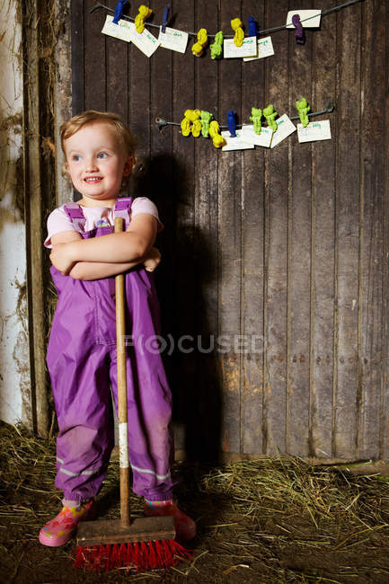 Girl in overalls sweeping in barn — Stock Photo