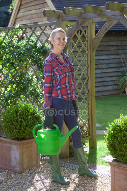 Woman carrying watering can in garden — Stock Photo