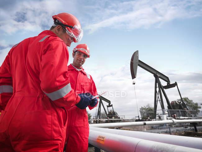 Deux travailleurs regardant un presse-papiers au premier plan avec des pompes à huile au-dessus des puits de pétrole terrestres (hochant la tête aux ânes / pompiers) en arrière-plan — Photo de stock