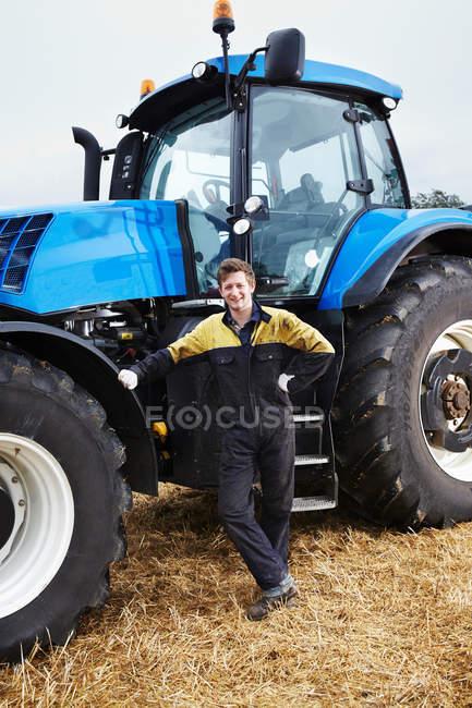 Paysan debout par tracteur dans le champ — Photo de stock