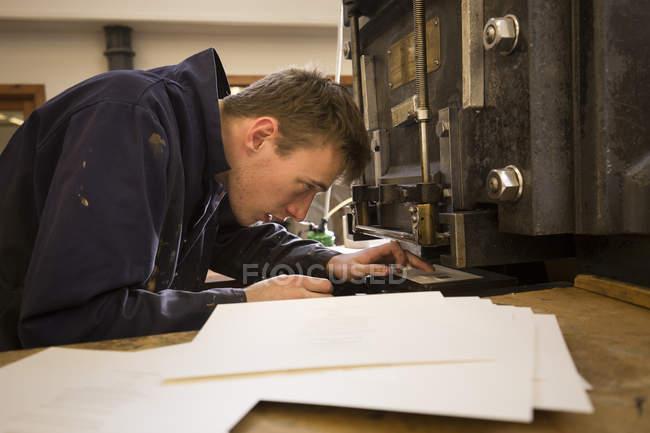 Giovane stampante maschile che prepara macchine per la stampa in officina di stampa — Foto stock