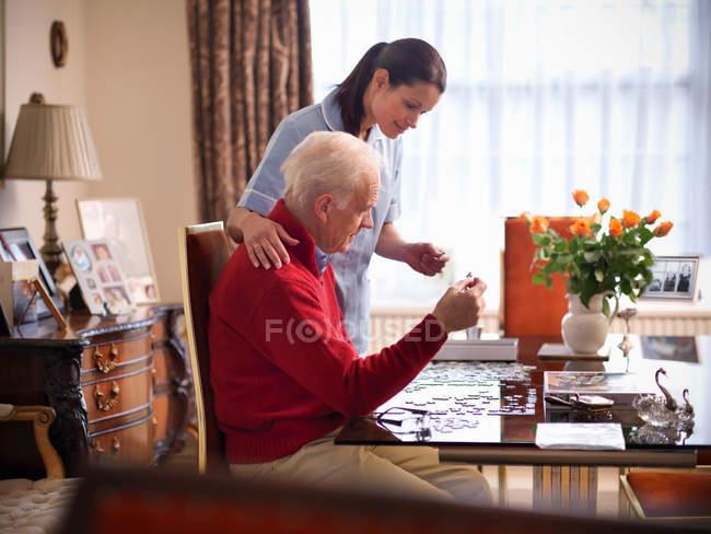 Медсестра помогает старшему человеку завершить головоломки — стоковое фото