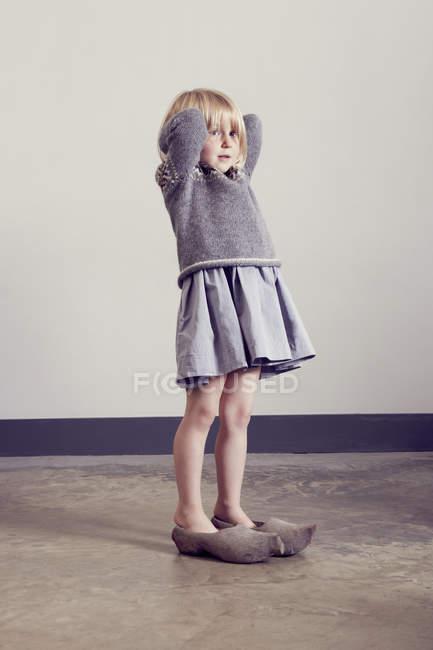 Chica de pie en zuecos de madera vintage con las manos detrás de la cabeza - foto de stock