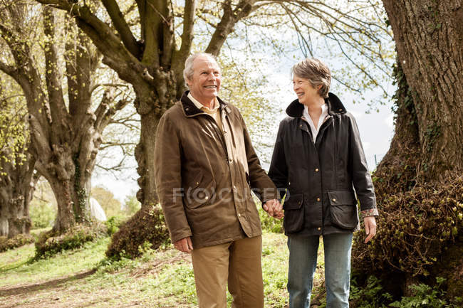Husband and wife holding hands walking in park — Stock Photo