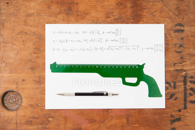 Gun shaped ruler and pen on paper, top view — Stock Photo