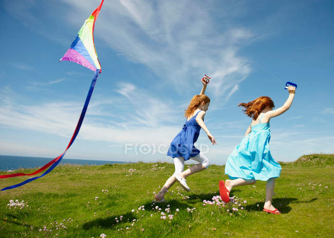 2 young girls running with kites — Stock Photo