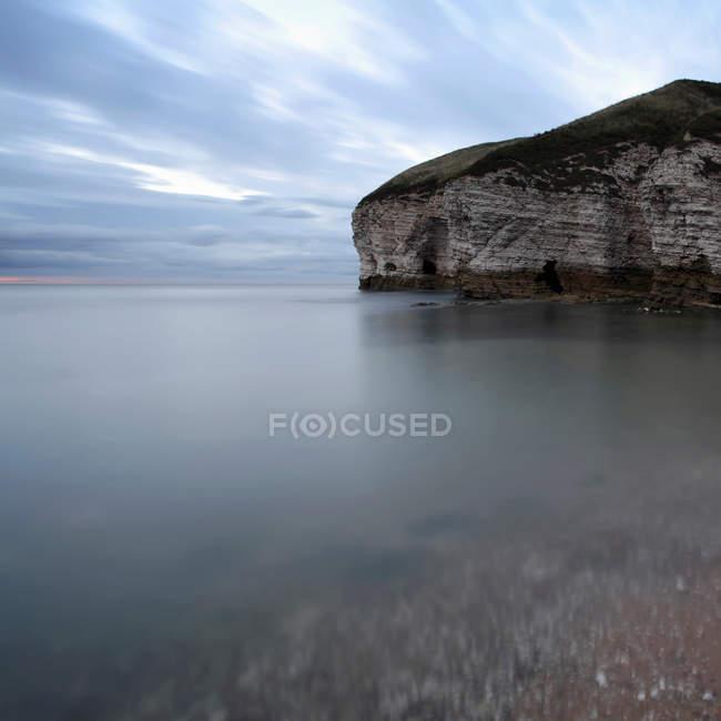 Tir longue exposition des falaises au bord de mer avec ciel nuageux — Photo de stock