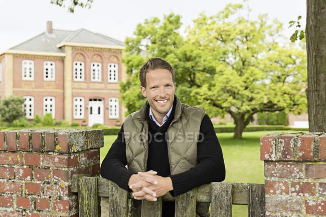 Взрослый мужчина опирается на деревянные ворота — стоковое фото