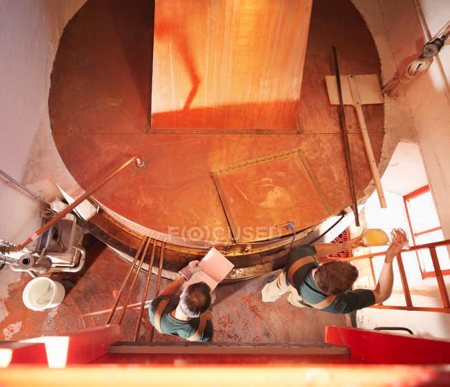 Travailleurs avec échantillon au réservoir de cuivre — Photo de stock