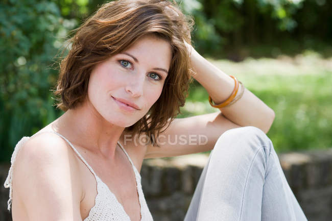 Smiling woman sitting outdoors, focus on foreground — Stock Photo