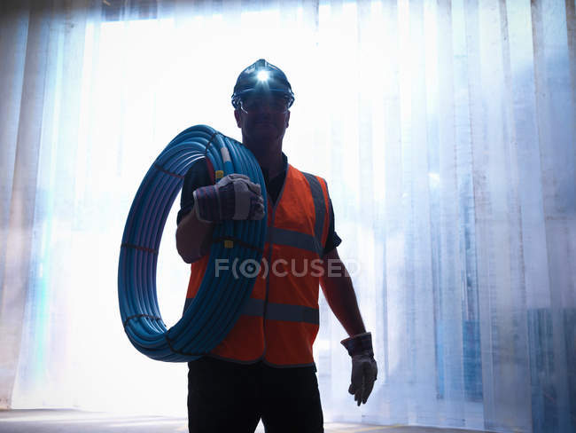 Silhouette of worker with water pipes and head lamp — Stock Photo