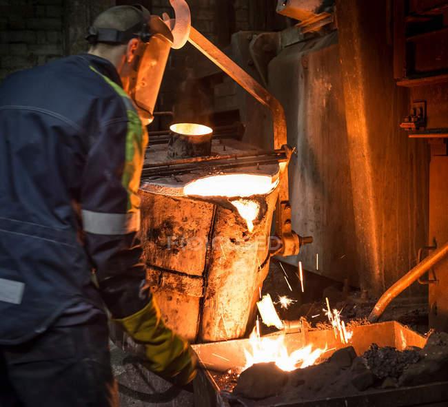 Рабочая очистка и подготовка поверхности расплавленного металла в литейном производстве — стоковое фото