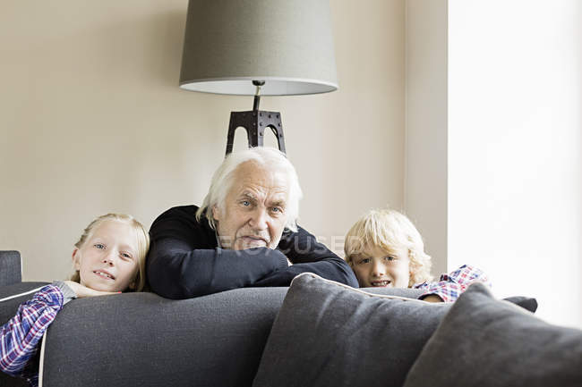 Portrait of grandfather and grandchildren leaning on sofa — Stock Photo
