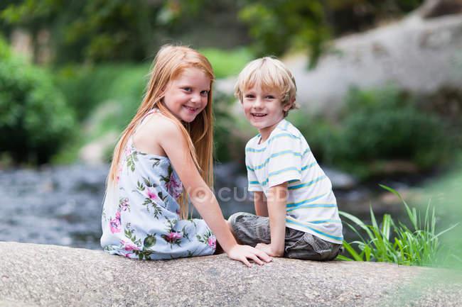 Bambini seduti sulla roccia insieme — Foto stock