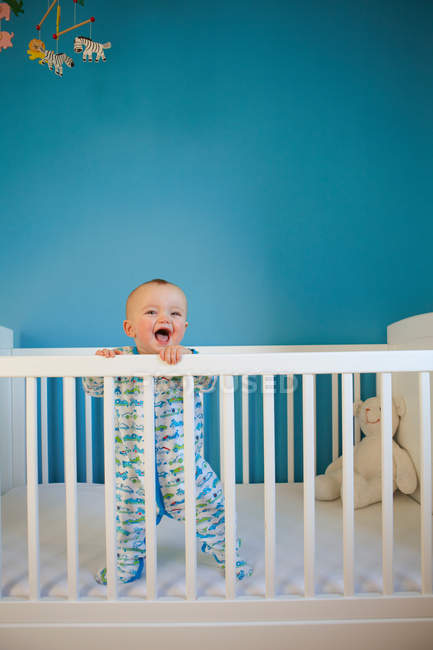 Toddler standing up in crib — Stock Photo
