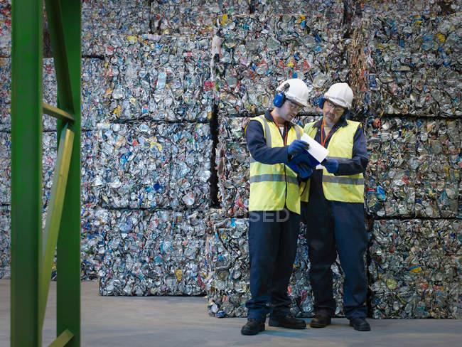 Reciclar trabajadores con balas de latas - foto de stock