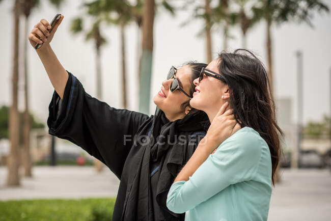 Молода східна жінка в традиційному одязі бере смартфон-селфі з подругою-жінкою Дубай, Об'єднані Арабські Емірати. — стокове фото