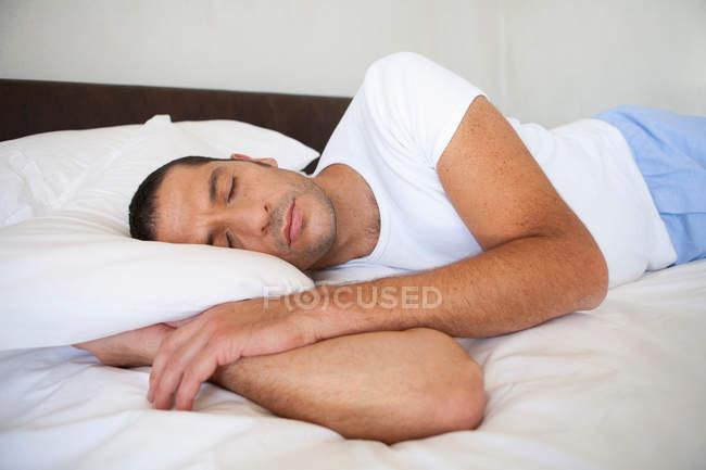 Людина спить на ліжку у себе вдома — стокове фото