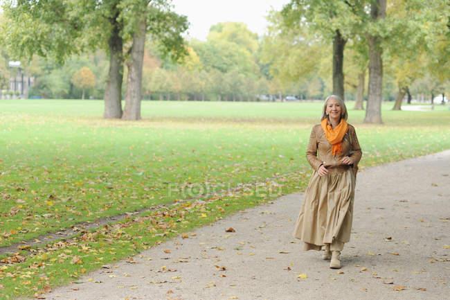 Senior woman walking in park — Stock Photo