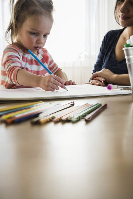 Female toddler at table with mother drawing in sketchbook — стокове фото