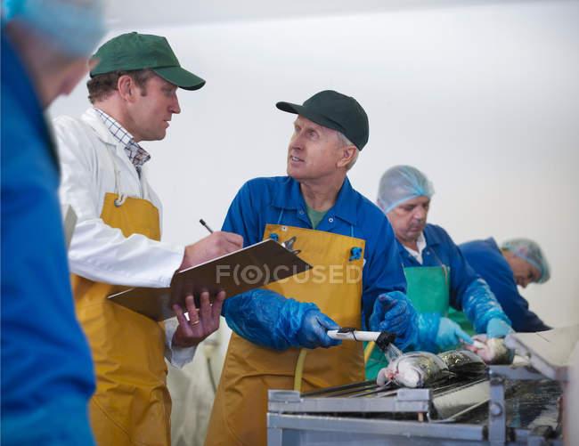 Менеджер і співробітники в обговоренні на лінії з виробництва ручної шотландських фермах лосося — стокове фото
