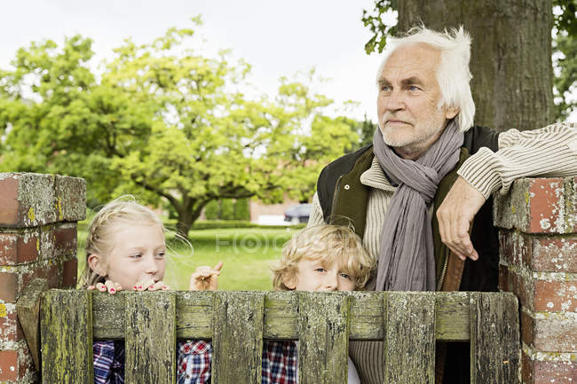 Grandfather and grandchildren by wooden gate — Stock Photo