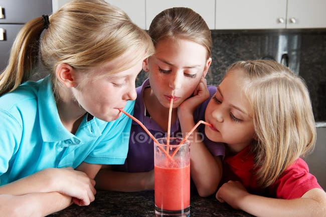 Girls drinking fruit juice with straws — Stock Photo