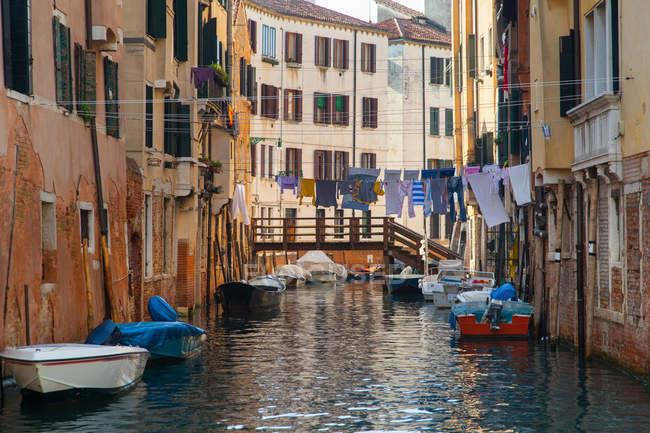 Barcos a remos e edifícios no canal urbano — Fotografia de Stock