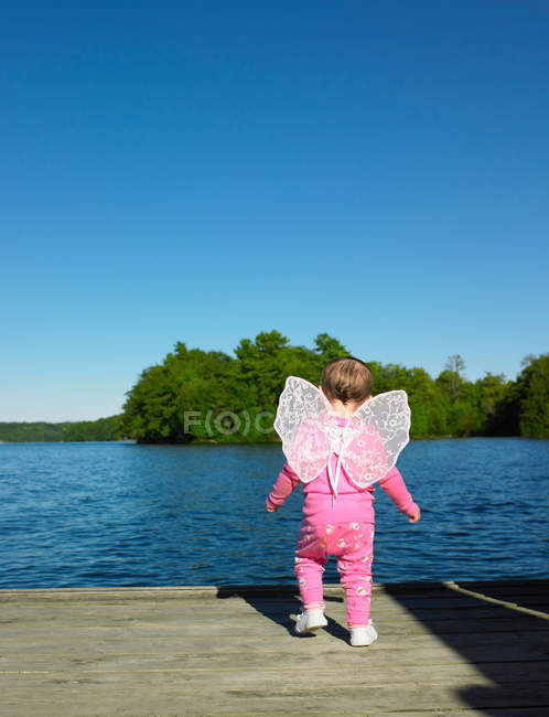 Toddler wearing fairy wings on dock — Stock Photo